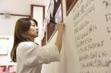 壁に卒業メッセージを書き込む優子 (C)AKS