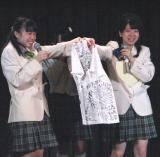 メンバー全員からのプレゼントの全員の寄せ書き入りのシャツを、清水花梨(左)からプレゼントされる小川。(C)De-View