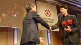 表彰式の様子(左から賞審査委員長の深澤直人氏、デンソーウェーブの吉田佳史さん)