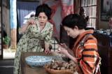 左から、キャサリン(濱田マリ)、亀山すみれ(早見あかり)。 こひのぼり・店内にて。春さん(及川いぞう)のはからいで、しばらく、住み込みで店の手伝いをすることになった、すみれ。分厚い里芋の皮をつまみ「やっぱり、マッサン(玉山鉄二)の妹やわ」と、あきれているキャサリン。『ザ・プレミアム マッサン スピンオフ(前編)「すみれの家出〜かわいい子には旅をさせよ〜」』4月25日、BSプレミアムで放送(C)NHK