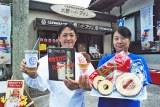 社務所横にオープンする喫茶コーナー兼売店の「大野cafeアプリ」を背に商品を持つ大野神社の大宮さん(左)とアプリの田中さん