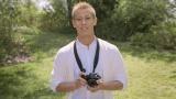 カメラを持って笑顔を見せる本田選手