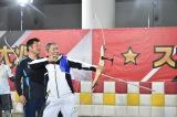 「的の真ん中に当てるには時間がかかるが、矢を打つことは誰にでもできます」と山本博の指導を受けるビートたけし(C)テレビ朝日