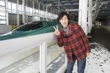 北海道新幹線の前で写真を撮る大泉洋。2月21日放送、TBS系『新幹線通ったら人生変わった〜大泉洋が応援!大逆転にかける北海道の人々〜』