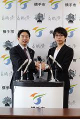 秋田県横手市役所で記者会見した高橋優と横手市長の高橋大氏(左)