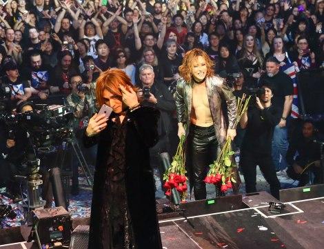 ファンから花束をもらって笑顔のYOSHIKIと記念撮影するSUGIZO
