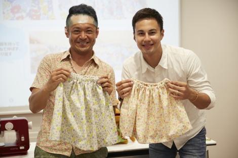 完成したスカートを手に笑顔のユージ(右)