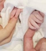生まれたばかりの双子と手をつなぐ写真を投稿した石田明