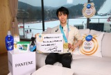 「応援ありがとうございました!皆さんと共に取った金メダルです!これからも頑張ります!」と書いたメッセージボードを持ち笑顔を見せる羽生選手