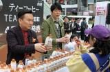 かまいたちがイベントで渋谷の街を歩く人々に新商品『WONDA TEA COFFEE』を手渡し