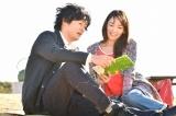 亡き恋人の前で微笑む中堂(C)TBS