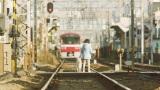 京急電車を眺める主人公サヤカ(新津ちせ)と愛犬・ルー(C)2018映画『駅までの道をおしえて』製作委員会