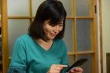 最新作『森村誠一ミステリースペシャル ガラスの密室』より。スマホを手にしてうれしそうな澄枝さん(岡江久美子)(C)テレビ朝日