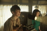 連続テレビ小説『まんぷく』第4回より。たちばな工房で幻灯機を実演する萬平(長谷川博己)と、壁に映し出された大阪の風景写真を見て、感激している福子(安藤サクラ)(C)NHK