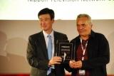 審査員長のドラガン・ペトロビッチ氏からトロフィーを授与された日本テレビの廣�P健一取締役(左)(C)日本テレビ