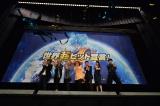 特製垂れ幕の前にキャストがせいぞろい(左から長峯達也監督、中尾隆聖、堀川りょう、野沢雅子、島田敏、水樹奈々、杉田智和)
