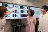 気象情報を提供しているトレインチャンネルの画面の前で説明を受ける=映画『天気の子』(7月19日公開)の声優、醍醐虎汰朗&森七菜が日本気象協会を訪問