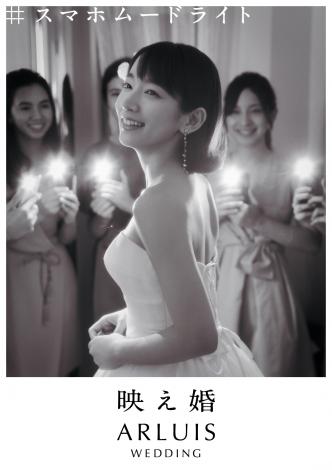 ゲストがスマホのライトを点灯させて、新婦の向こうからカメラにむけて逆光になるように撮影「#スマホムードライト」