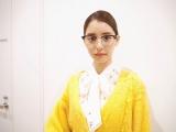 """花柄ブラウスに黄色のカーディガンでピッタリ横分けヘアに黒ぶちメガネを掛けた""""堅実ユリカ"""" (写真は公式ブログより)"""