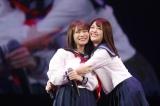 1期生の秋元真夏と松村沙友理はセーラー服で頬を寄せ合って笑顔