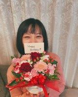 夫のK-1ファイター・卜部弘嵩選手から贈られた花を持ち笑顔の高橋ユウ (写真は公式ブログより)